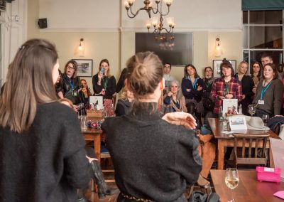 group applauding women giving a talk